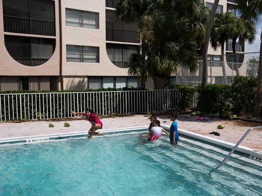 Astrid Santos, 9, jumps into the pool at Angler's Cover Condominiums as her mother Reina Santos, white shirt, and cousins Johanna Leon and Jonathan Leon, 7, look on  Marco Island, Fla. Monday, September 11, 2017.