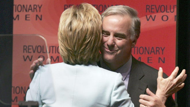 Hillary Clinton, then a senator, and former Vermont Gov. Howard Dean embrace on stage during a 2004 event in Boston.