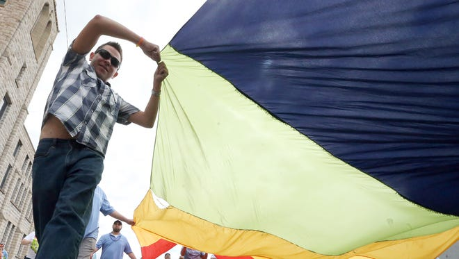 """Participants carry a giant rainbow flag along Montana Avenue during the Sun City PrideFest 2017 Parade near Downtown El Paso. The parade featured floats, balloons, music and was led by a Fort Bliss honor guard. It was part of a weeklong observance in honor of LGBTQI Month. The parade started at Houston Park and traveled West to Downtown. The theme for the events was """"Hear Me Roar."""" The El Paso Chihuahuas Mascot """"Chico"""" was one of the parade's grand marshals."""