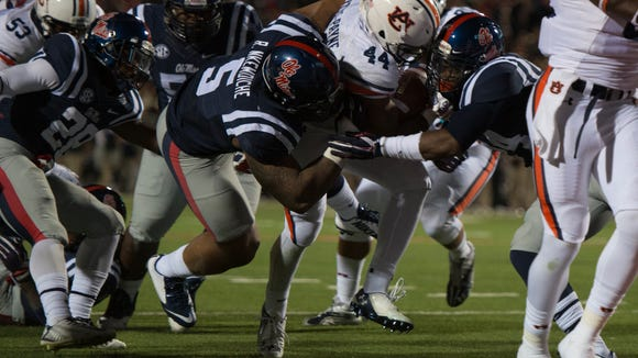 Auburn running back Cameron Artis-Payne (44) scores a touchdown as Mississippi defensive tackle Robert Nkemdiche (5) attempts to stop him during the NCAA football game at University of Mississippi in Oxford, Miss., on Saturday, Nov. 1, 2014. Auburn defeated Mississippi 35-31