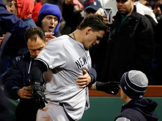 New York Yankees first baseman Tyler Austin (26) is escorted off of the field after a scrum against the Boston Red Sox during the seventh inning at Fenway Park.