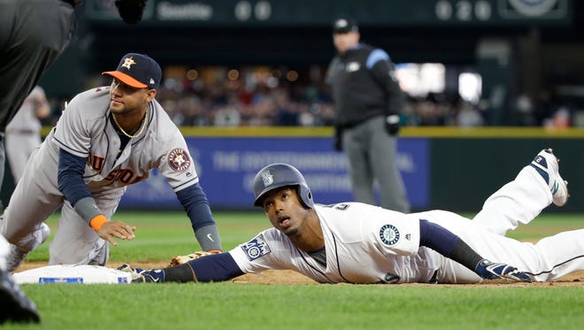 The Mariners' Jean Segura (right) and Houston first baseman Yuli Gurriel look up for the call after Segura dove back to first base on a line drive by Mitch Haniger in the third inning of an April 10 game. Segura went on the 10-day disabled list after the game and didn't return until Tuesday.