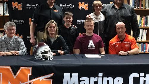 Max Kretzschmar (middle) poses with family and friends after signing to play football at Alma College