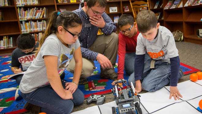 Members of Sonoma Elementary School's Robotic Club, 4th-graders Sydney Calvert, left, Donovan Meeks, Braydon Rivas and teacher Chistopher Stillion examine one of the club's award winning robots in the school library. The Robotics Club won three awards at the Vex Robotics Competition White Sands Qualifying Event.