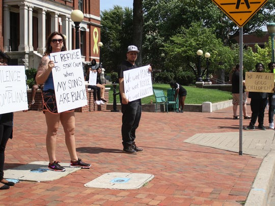 Demonstrators hold signs against violence during a