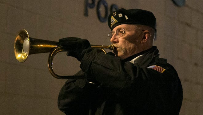 Navy veteran Jim Artz plays taps during a Memorial Service remembering the events of Pearl Harbor on Wednesday evening at the AMVETS Post 26.