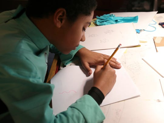 Bryce Bullock doodles at his drawing desk in the basement