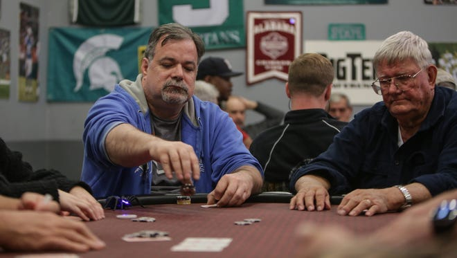Bob Park, left, of Davison tosses some chips in as Tom Daane of Lapeer waits during a game of Texas Hold'em poker at Legends Poker Place in Metamora on on Thursday, Oct. 29, 2015, while playing for charity benefiting the Lapeer Chamber of Commerce.