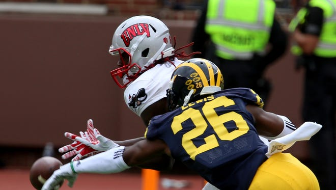 Michigan's Jourdan Lewis knocks the football out of the hands of UNLV wide receiver Devonte Boyd on Sept. 19, 2015.