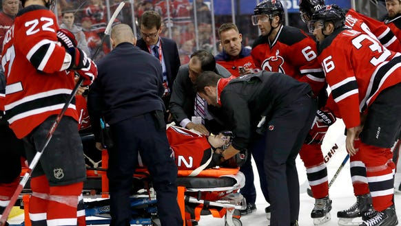 Trainers load Devils defenseman John Moore onto a stretcher