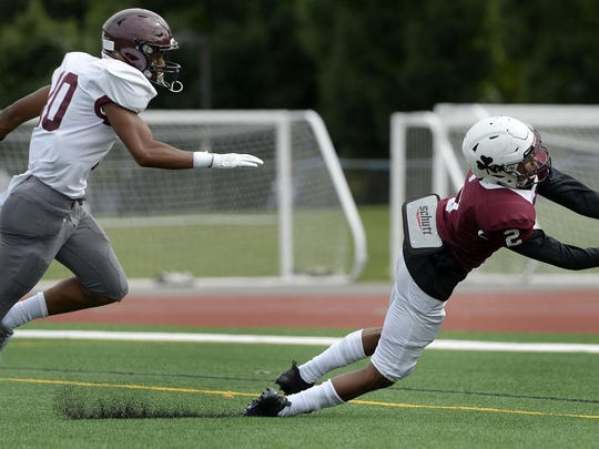 Aquinas' Kobe McNair, right, makes a diving touchdown catch during a Saturday, Sept. 22, 2018 game. McNair did everything he could Saturday against Friendship Collegiate.