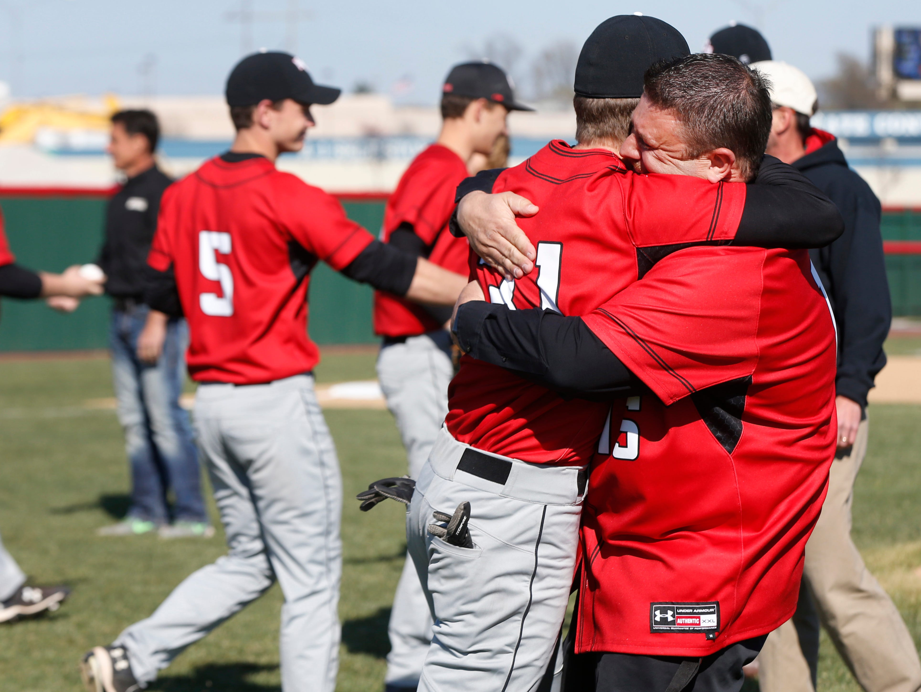 Matt Searson hugs his son Matthew Searson after he threw out the first pitch before the New Covenant Academy baseball team played their first game at Federal Protection Field on Monday, Mar. 21, 2016.
