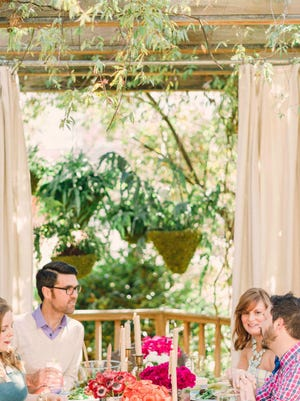 A pergola adds shade to the outdoor dining space, while weather-resistant drapery adds privacy.