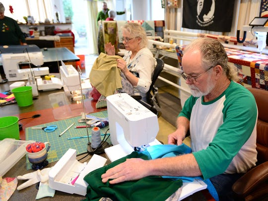 Tom Korn works on a quilting project with family and friends at his northeast Salem home on Monday, Dec. 15.