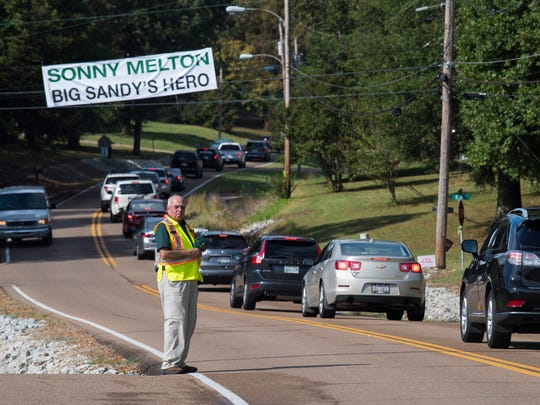 Benton County Rescue Squad employee Don Myers, of Camden, holds his hat to his heart Tuesday, October 10, 2017, as vehicles exit Big Sandy High School en route to Sonny Melton's burial site.