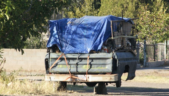 A detached truck bed loaded with trash is the only visual sign of the problem at a quiet Copper Street house where a messy backyard was declared a nuisance Monday evening.