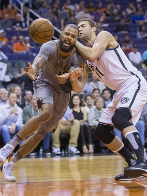 Nets' Brook Lopez (11) knocks the ball away from Suns'