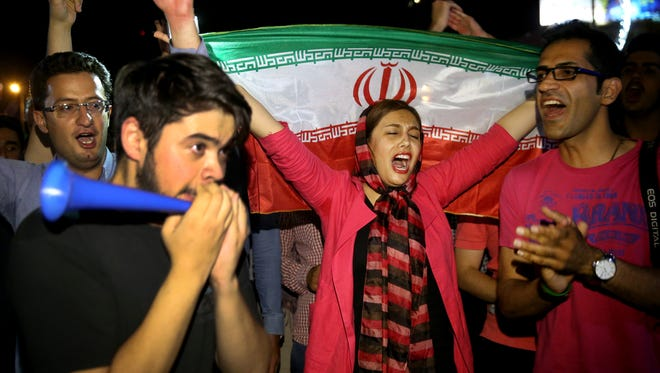 An Iranian woman holds up an Iranian flag as people celebrate a landmark nuclear deal, in Tehran, Iran, Tuesday, July 14. Overcoming decades of hostility, Iran, the United States, and five other world powers struck a historic accord Tuesday to check Tehran's nuclear efforts short of building a bomb. The agreement could give Iran access to billions in frozen assets and oil revenue, stave off more U.S. military action in the Middle East and reshape the tumultuous region.