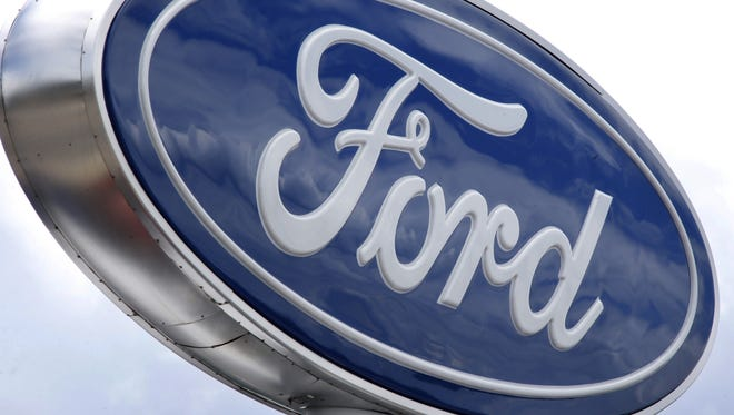 FILE - In this Thursday, June 5, 2014, file photo, clouds are reflected in the Ford sign at a dealership in Wexford, Pa. Ford on Wednesday, Sept. 30, 2015 said it is recalling some older Windstar minivans to because a previous rear-axle recall repair might not work. (AP Photo/Keith Srakocic, File)