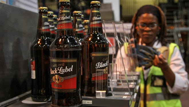 FILE PHOTO: An employee monitors labelling quality on bottles of Carling Black Label beer in the bottling plant at the SABMiller Plc brewery in Cape Town, South Africa, on Friday, March 14, 2014. SABMiller acquired almost 50 companies in the last decade, including Foster's Group Ltd. for about $13 billion in 2011, according to data compiled by Bloomberg. Photographer: Dean Hutton/Bloomberg ORG XMIT: 479765699