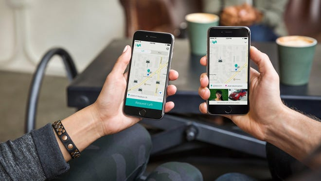 Users looking at the Lyft mobile app, a ride-sharing service available in Indianapolis.