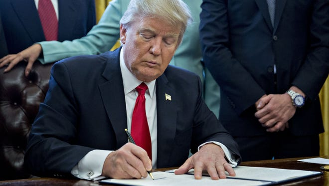 """U.S. President Donald Trump signs an executive order in the Oval Office of the White House surrounded by small business leaders January 30, 2017 in Washington, DC. Trump said he will """"dramatically"""" reduce regulations overall with this executive action as it requires that for every new federal regulation implemented, two must be rescinded."""