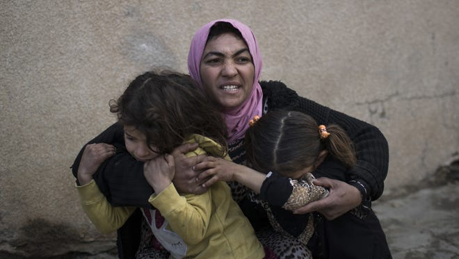 A woman holds her daughters on March 14 as gunshots are heard in a neighborhood in western Mosul, Iraq. At least 300 civilians have been killed in the offensive against the Islamic State in the western half of Mosul since mid-February.