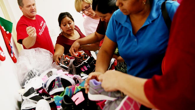 Volunteers help parents pick out shoes for their children during the Holiday Gift Shop at the Guadalupe Center in Immokalee on Wednesday, Dec. 14, 2016. Parents could pick out up to three gifts for free per child for Christmas.