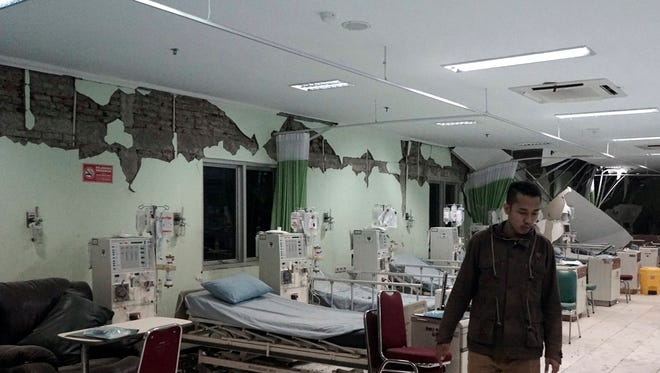 An Indonesian man is pictured walking inside a damaged room in the Banyumas regional public hospital after a 6.5-magnitude earthquake in Banyumas, Central Java, Indonesia killed at least two people.