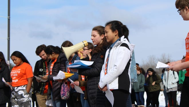 Arlington High School students speak during a walkout on Wednesday.