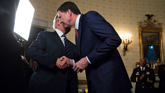 President Trump (L) shakes hands with James Comey,