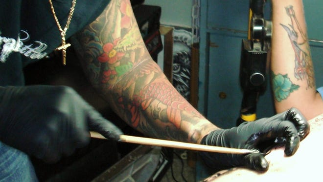 Tattoo artist Dragon Edong Elenzano, Megavision El Drako Tattoo, working on a client using the tebori hand tattooing method.