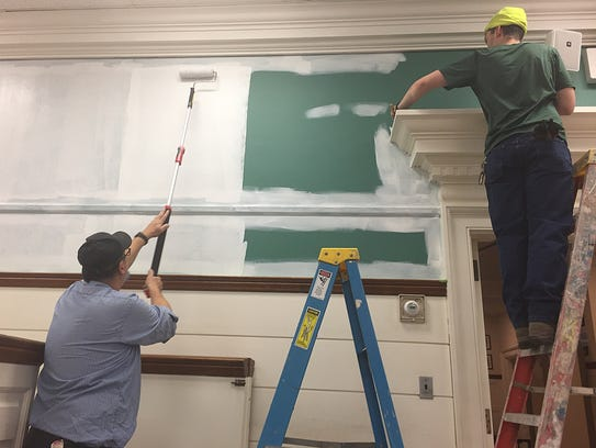 Public works laborers Salvatore Cuocci and Xavier Hernández prime walls of the courtroom in the borough hall to be repainted.