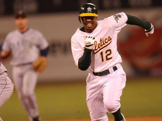Oakland Athletics outfielder Terrence Long runs back to first base during a run down as Seattle Mariners shorstop Carlos Guillen looks on in the eighth inning in Oakland, Calif., on Friday, Sept. 13, 2002. Long got an RBI single on the play. Oakland won the game 5-0. (AP Photo/Marcio Jose Sanchez)