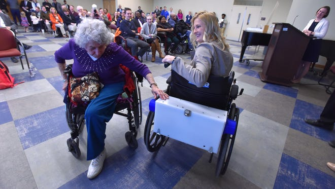 Lawrence Tech biomedical engineering student Hayley Walkowski of Novi shows Evelyn Horwitz, 90, of Ann Arbor a removeable device that can transform any manual wheelchair into an automatic. Students were demonstrating prototypes of devices they invented.