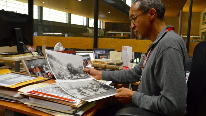 """Chris Haley, director of the study of the legacy of slavery in Maryland at the Maryland State Archives, reviews pictures of a staff member's ancestors, one of whom is pictured with his manumission, the certificate of freedom during the time of slavery. Haley is the nephew of """"Roots"""" author Alex Haley."""