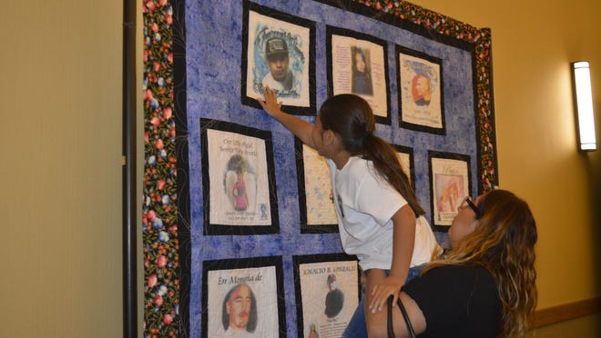 Janet Quevedo holds Aimee Quevedo up to get a closer view of their family member Rafael Bobadilla. The quilts were made to honor victims of violent crimes. Photo taken on April 14, 2016.