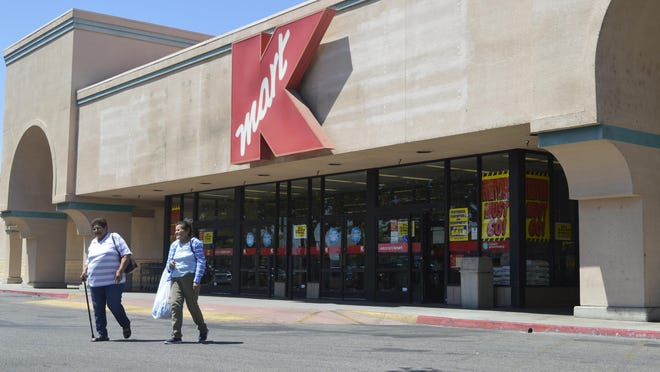 Shoppers walk away from the Tulare Kmart earlier this week. The store is closing due to a company-wide decision to close 69 locations.