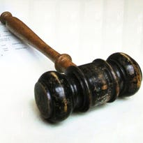 A gavel rests on a judge's desk.