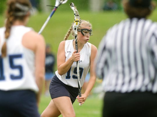Mount Mansfield's Alana Scott, center, charges toward the net on a free-position attempt during the first half of Wednesday's girls lacrosse semifinal against South Burlington in Jericho.