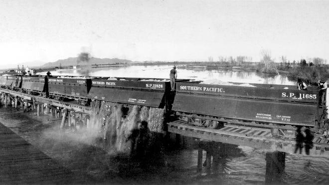 Southern Pacific Railroad cars drop rocks into the sea in an effort to dam the Colorado River, circa 1907.