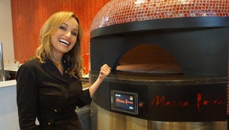 Giada De Laurentiis shows off the Marra Forni pizza oven, made by a company in Beltsville, Md. It heats the pizzas at 700 degrees.