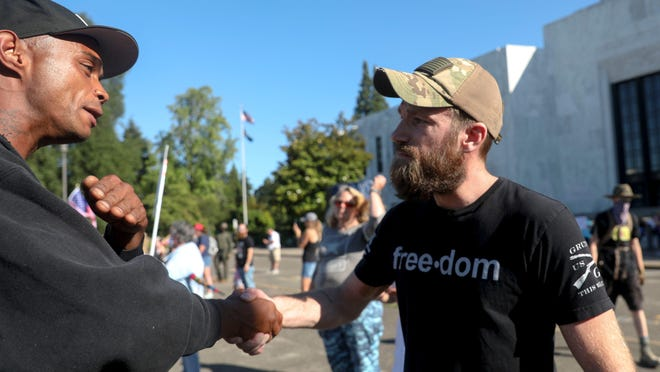 Clarence Carr and Justin Steinbock shake hands after discussing political issues during a protest in opposition to police violence and counter-protest at the Oregon State Capitol, in Salem, Oregon, on Saturday, July 25, 2020.