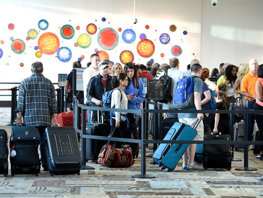 Travelers stand in line at Nashville International Airport in this file photo.