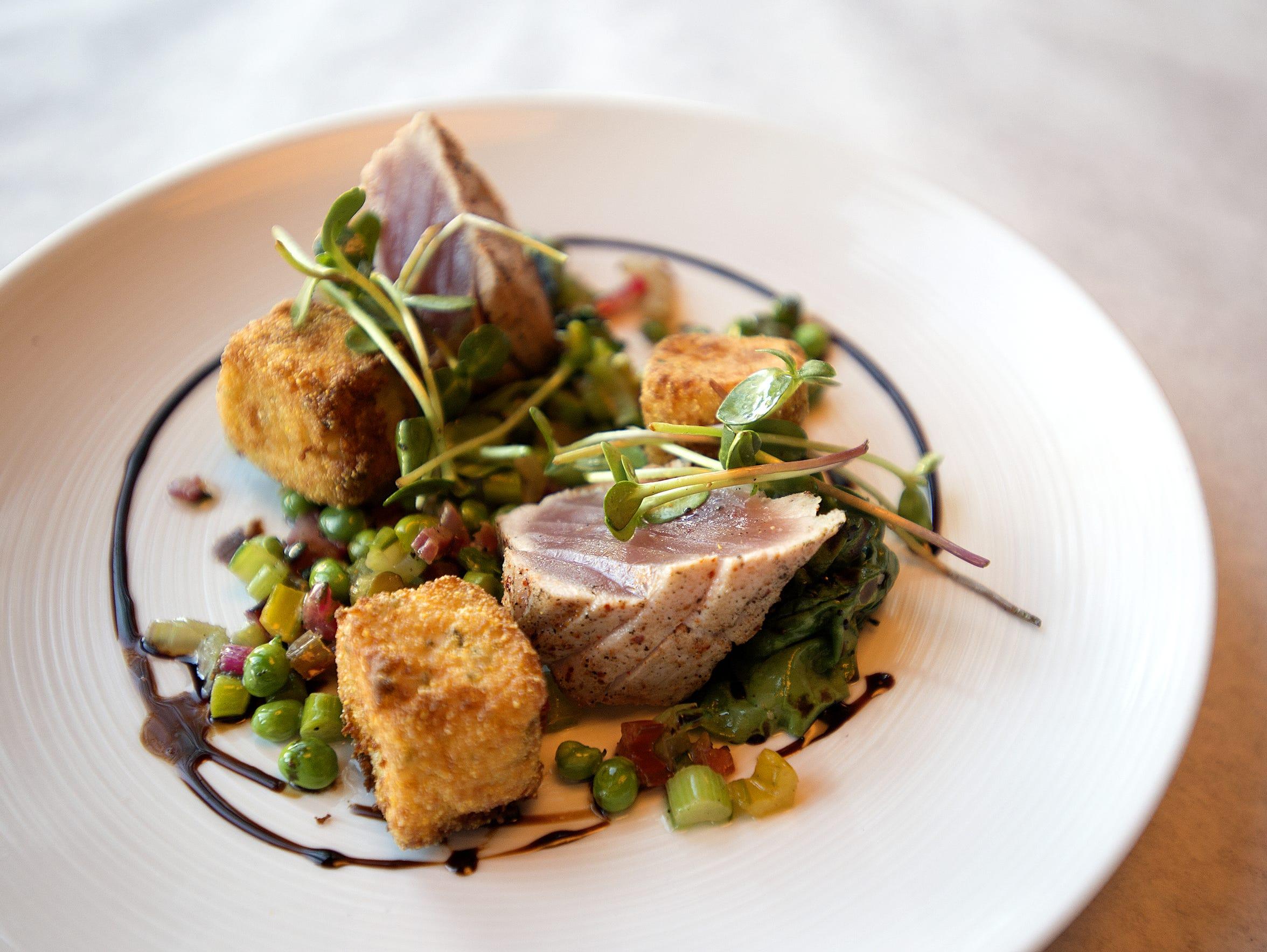 Seared ahi tuna served rare with a mix of peas, asparagus