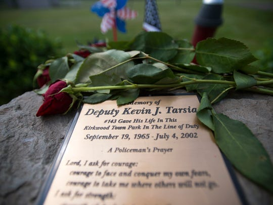 Roses lay at a memorial for fallen deputy Kevin Tarsia in Grange Hall Park, where Tarsia was killed in 2002.