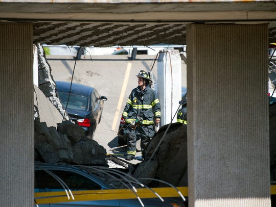 A firefighter stands where the upper-deck of a parking