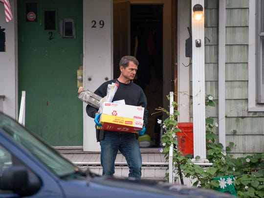 A DEA agent removes evidence from a home on Walnut Street in Binghamton following a drug bust early Wednesday morning.