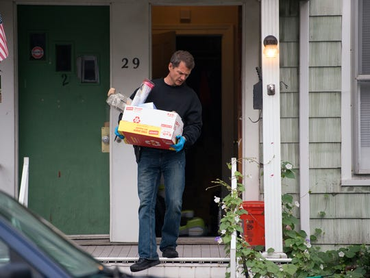 A DEA agent removes evidence from a home on Walnut