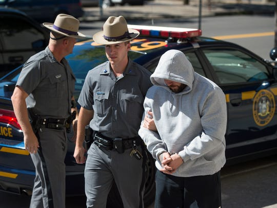 Jeremiah O'Brien, one of four men arrested, is brought
